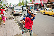 Apr 23 - BALI, INDONESIA -  An Indonesian man carries his daughter down the street in the town of Kintamani in the mountains of central Bali.  Photo by Jack Kurtz/ZUMA Press