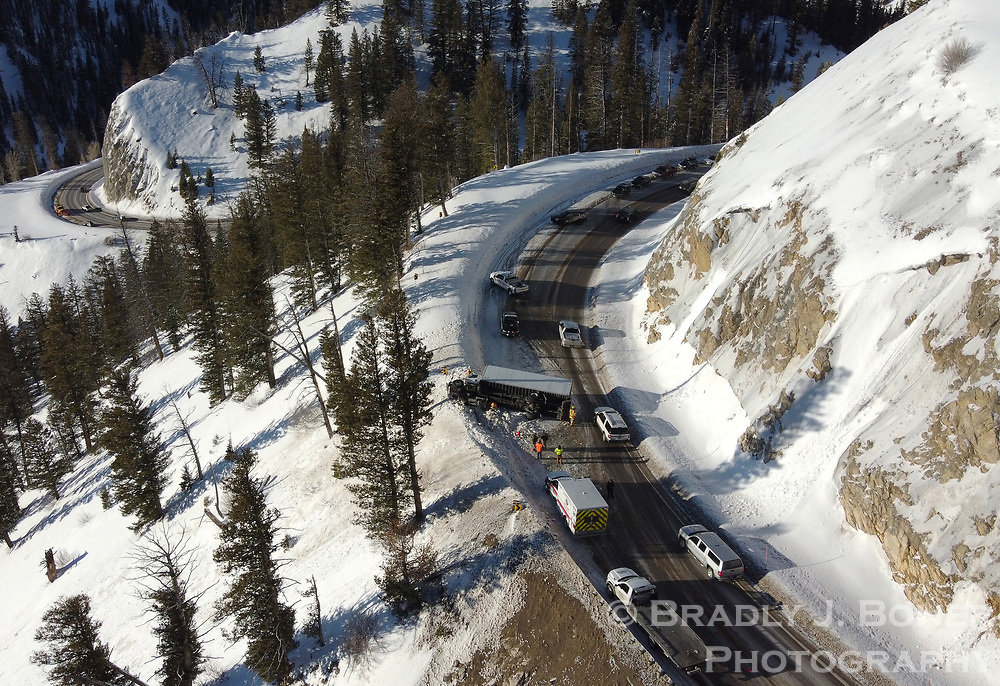 Cars snake past an overturned box truck that wrecked while descending the west side of Teton Pass on Monday, snarling traffic for evening commuters. The condition of the driver was unknown as of press time.