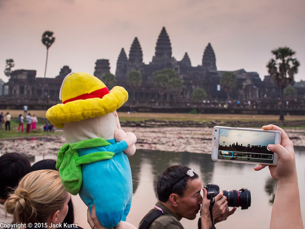 """14 MARCH 2105 - SIEM REAP, SIEM REAP, CAMBODIA: A tourist photographs Angkor Wat with his smart phone at sunrise while another tourist use a digital SLR. The area known as """"Angkor Wat"""" is a sprawling collection of archeological ruins and temples. The area was developed by ancient Khmer (Cambodian) Kings starting as early as 1150 CE and renovated and expanded around 1180CE by Jayavarman VII. Angkor Wat is now considered the seventh wonder of the world and is Cambodia's most important tourist attraction.   PHOTO BY JACK KURTZ"""