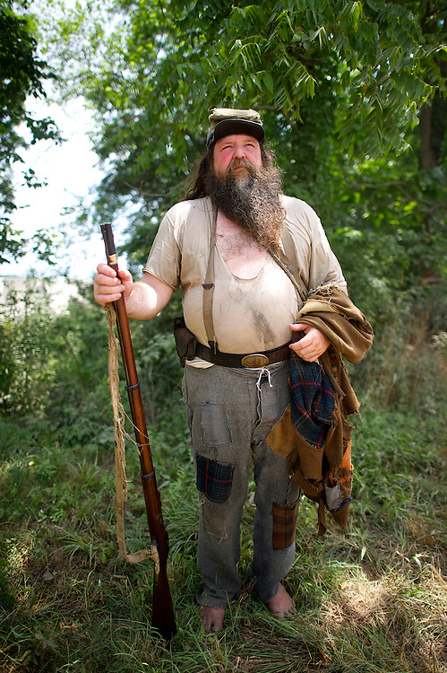 """Scott Bumgarner, 55, from North Carolina, a 'hardcore' reenactor since 1988 with the 28th North Carolina Infantry, who participates barefoot, and had 12-15 relatives that served for the Confederate army, poses for a portrait on the final day of a four day Gettysburg Anniversary Committee 150th Gettysburg reenactment in Gettysburg, PA on July 7, 2013.  """"Reenacting is living history; it keeps the history alive and gets people to get a taste of it,"""" he said.  """"Everything is here but the blood but they can get that in the movies."""""""