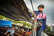 14 NOVEMBER 2012 - BANGKOK, THAILAND:  A ticket taker and fare collector holds onto a the safety rope on a passenger boat on Khlong Saen Saeb in Bangkok. Bangkok used to be criss crossed by canals (called Khlongs in Thai) but most have been filled in and paved over. Khlong Saen Saeb is one of the few remaining khlongs in Bangkok with regular passenger boat service. Boats and ships play an important in daily life in Bangkok. Thousands of people commute to work daily on the Chao Phraya Express Boats and fast boats that ply Khlong Saen Saeb. Boats are used to haul commodities through the city to deep water ports for export.      PHOTO BY JACK KURTZ