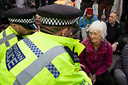 Elderly climate change activist from the Extinction Rebellion group are cautioned by police before being arrested for blocking the street at Bank in the heart of the City of London financial district in protest that the government is not doing enough to avoid catastrophic climate change and to demand the government take radical action to save the planet, on 25th April 2019 in London, England, United Kingdom. Extinction Rebellion is a climate change group started in 2018 and has gained a huge following of people committed to peaceful protests.