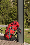 Red hikers backpack lying against a column, Routeburn Shelter, South Island, New Zealand