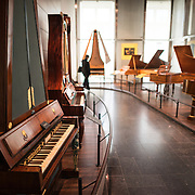 Historical pianos on display at the Musical Instrument Museum in Brussels. The Musee des Instruments de Musique (Musical Instrument Museum) in Brussels contains exhibits containing more than 2000 musical instruments. Displays include historical, exotic, and traditional cultural instruments from around the world. Visitors to the museum are given handheld audio guides that play musical demonstrations of many of the instruments. The museum is housed in the distinctive Old England Building.