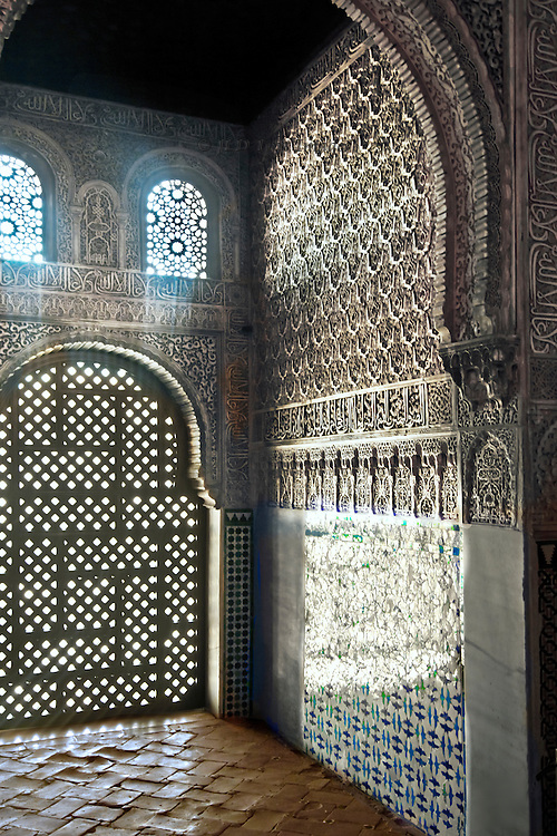 Niche in the Hall of the Ambassadors, Alhambra.  Tiled floor and wainscot, marble wall, decorated arches, grilled windows.  Sunlight streaming through the windows sheds a magical glow into the space.  Unusually, it is empty of tourists.