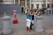 London busker wearing union jack suit stands waiting donations as tourist parents attend to baby in Trafalgar Sq.