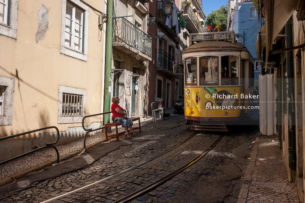 As a local lady looks on from her street bench, as a number 28 tram edges slowly through a steep and narrow street, on 11th July 2016, in Lisbon Portugal. The 28 is one of the trams not only used by the people of the capital but also of an increasing number of tourists who ride the entire route from Prazeres cemetery in the west of the city, to Rossio in the centre, after a loop through some of the most amazing streets and landmarks. So crowded is the 28, that older locals often can't sit down, having to stand over younger, inconsiderate tourist families who want a window seat for the entire journey - and back. Notices at termini remind visitors that this is a public service and to consider locals. Photo by Richard Baker / In Pictures via Getty Images)