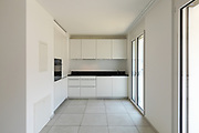 White kitchen with windows in empty modern apartment. Nobody inside