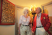 Wolf C Hartwig aged 91, producer of epic films and soft-porn features, with his fourth wife, and actress, Veronique Vendell in their apartment on Avenue de Foch, Paris. Wolf Hartwig was awarded a Bambi Award from German Cinema for his film 'The Iron Cross' which was directed by Sam Peckinpah starring James Coburn with Veronique Vendell. A producer working in exploitation genres, soft porn, sex, lurid, violent and sensational features. Other films he produced include 'Horrors from Spider Island'. 'Lady Hamilton' and 'Virgin of the Seven Seas'.//Wolf Hartwig and his wife Veronique Vendell with Chinese intricate carved relief