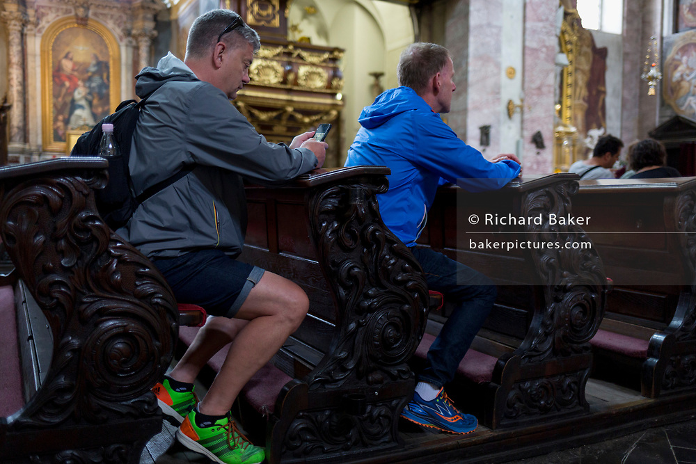Visitors to the Cathedral of saint Nicholas use a phone while sitting in pews, in the Slovenian capital, Ljubljana, on 28th June 2018, in Ljubljana, Slovenia.