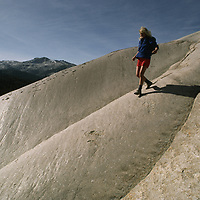 Yosemite National Park, California. Hiker scrambles down glacier polished granite on Daff Dome.