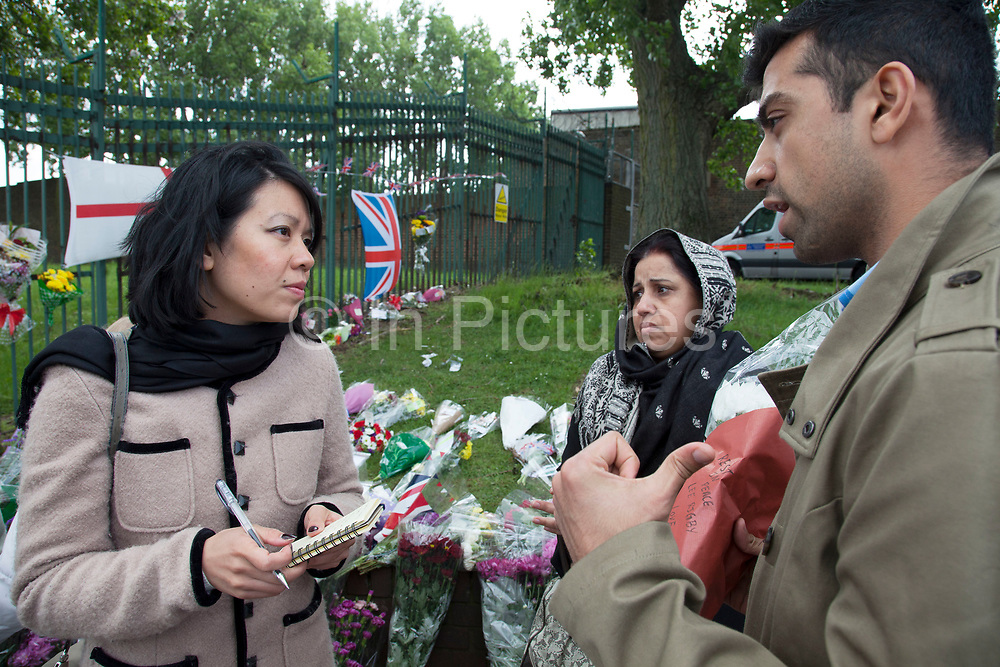London, UK. Saturday 25th May 2013. Shoaib Zefar (25) from Pakistan speaks to Khue Pham, with his parents at the memorial to Drummer Lee Rigby in Woolwich, London, UK. He says that what happened here is not Islam, but that all Islam was peaceful and how important it was fro them to come to pay their respects. Flowers from every section of the local community along with messages of condolence and support. On the afternoon of 22 May 2013, Lee Rigby, a British Army soldier and a Drummer of the Royal Regiment of Fusiliers, was killed by two attackers near the Royal Artillery Barracks in Woolwich, south-east London.