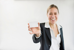 Portrait of businesswoman in black suit holding blank business card, smiling