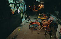At night in the backstreets  of Guangzhou, southern China a man relaxes and sleeps on chairs outside his home.