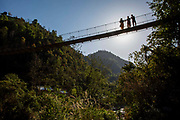 People walking across a suspension bridge in a small rural village on the 11th of March 2020 in the Dakshinkali area, Kathmandu District, Bagmati Pradesh, Nepal. Suspension bridges are constructed high above the rivers in Nepal to accommodate river level rises in the different seasons.