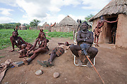 Viahondjera Musutua (far left), a Himba tribeswoman, sits outside her hut with members of her family in the Ondjete in northwestern Namibia. (Viahondjera Musutua is featured in the book What I Eat; Around World in 80 Diets.) The Himba culture is polygamous and Viahondjera is the second wife of her husband. Like most traditional Himba women, she covers herself from head to toe with an ochre powder, cow butter blend. The photograph was made in Okapembambu village, where she was raised. She is here with her youngest child helping with the corn harvest to bring back corn for her husband and children.