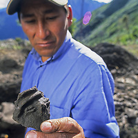 Cordillera Vilcabamba, Andes Mountains, Peru. Peruvian archaeologist Ives Bejar examines a pre-Columbian miniature sculpture from site at Corihuayrachina on Cerro Victoria that might be Incan or even earlier in origin.