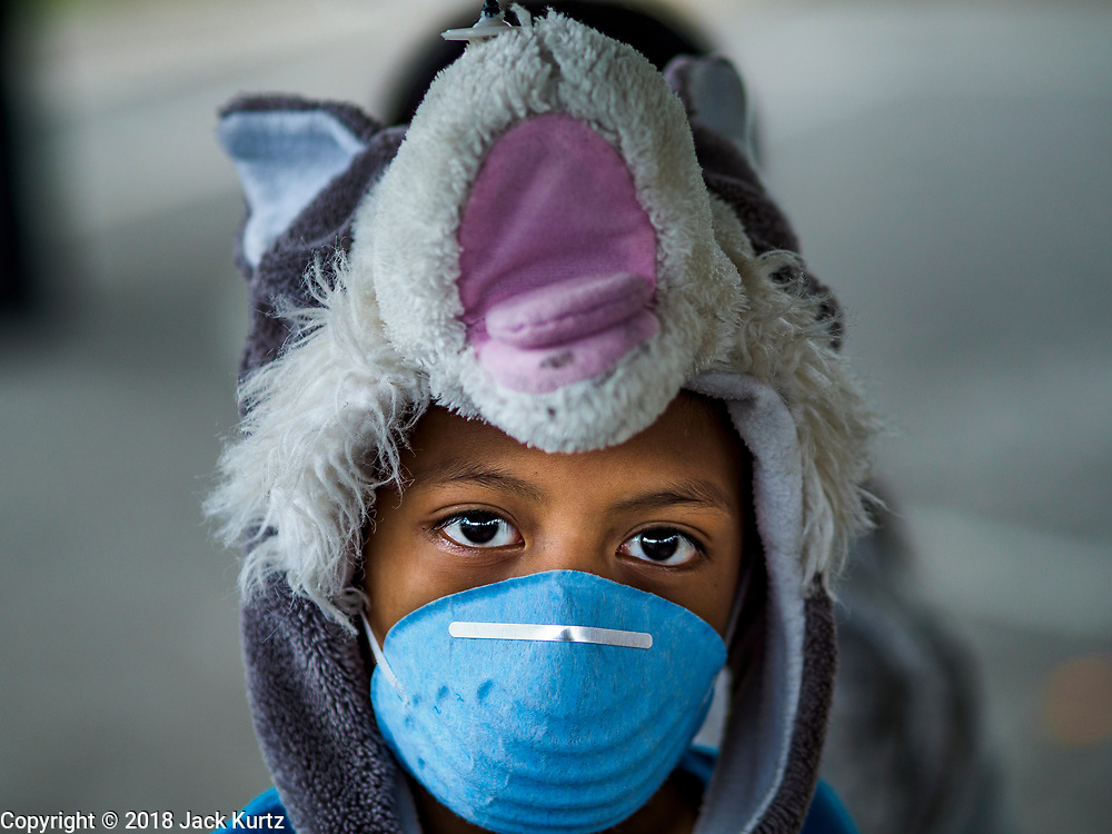 "22 JANUARY 2018 - GUINOBATAN, ALBAY, PHILIPPINES: A boy in an evacuation center in Guinobatan wears a face mask. Several communities in Guinobatan were hit ash falls from the eruptions of the Mayon volcano and many people wore face masks to protect themselves from the ash. There were a series of eruptions on the Mayon volcano near Legazpi Monday. The eruptions started Sunday night and continued through the day. At about midday the volcano sent a plume of ash and smoke towering over Camalig, the largest municipality near the volcano. The Philippine Institute of Volcanology and Seismology (PHIVOLCS) extended the six kilometer danger zone to eight kilometers and raised the alert level from three to four. This is the first time the alert level has been at four since 2009. A level four alert means a ""Hazardous Eruption is Imminent"" and there is ""intense unrest"" in the volcano. The Mayon volcano is the most active volcano in the Philippines. Sunday and Monday's eruptions caused ash falls in several communities but there were no known injuries.    PHOTO BY JACK KURTZ"