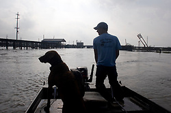 25 Sept, 2005.  Hackberry, Louisiana. Hurricane Rita aftermath. <br /> Local cajun man Aaron Stokes and his dog Maggie tour the swamps and bayou's checking on neighbours and their homes.<br /> Photo; ©Charlie Varley/varleypix.com