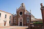 """Madonna dell'Orto church was erected by the now-defunct Humiliati religious order in the mid 1300s in the sestiere of Cannaregio, Venice. The brickwork bell tower was finished in 1503 with an onion dome in Eastern style, topped by a white marble statue of the Redeemer. Venice (Venezia) is the capital of Italy's Veneto region, named for the ancient Veneti people from the 900s BC. The romantic """"City of Canals"""" stretches across 100+ small islands in the marshy Venetian Lagoon along the Adriatic Sea in northeast Italy. The Republic of Venice was a major maritime power during the Middle Ages and Renaissance, a staging area for the Crusades, and a major center of art and commerce (silk, grain and spice trade) from the 1200s to 1600s. The wealthy legacy of Venice stands today in a rich architecture combining Gothic, Byzantine, and Arab styles."""