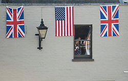 © Licensed to London News Pictures. 19/05/2018. London, UK.  A group of women watch from a window at a carriage passes through Windsor following the wedding of Prince Harry, The Duke of Sussex and Meghan Markle, The Duchess of Sussex at St George's Chapel in Windsor Castle. Photo credit: LNP