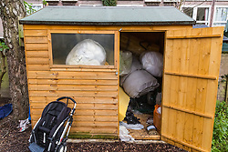 A shed adjacent to a small wooden wendy house in a section of an allotment reserved as a children's play area appears to have become the residence or storage shed of a homeless individual. Munster Square, Camden, March 18 2019.