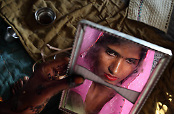 Radha, 15, observes herself in a cracked mirrorvthe day before her wedding. Despite legislation forbidding child marriage in India (Child Marriage Restraint Act-1929), the much more progressive Prohibition of Child<br /> Marriage Act (2006) and many initiatives to prevent child marriage, marrying children off at a very tender age continues to be accepted by large sections of society.