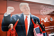 """06 DECEMBER 2020 - DES MOINES, IOWA: People pose for pictures alongside the """"March for Trump"""" bus during a rally to support the President. About 1,000 supporters of outgoing US President Donald Trump rallied in Des Moines Sunday to show their support for the President and to protest the outcome of the US Presidential election. They started with a rally in the suburbs of Des Moines then drove in a motorcade through the city, ending at the State Capitol. They repeated many of Trump's discredited claims that the election was marked by fraud and that Trump actually won. The protest was a part of the national """"March for Trump"""" effort, culminating in a march in Washington DC on December 13. Joe Biden won the election, with 306 electoral votes to Trump's 232.      PHOTO BY JACK KURTZ"""