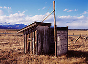 Outhouse behind the abandoned Nathrop school house with the Collegiate Mountain Range beyond, Nathrop, Colorado.