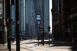 © Licensed to London News Pictures. 26/03/2020. Manchester, UK. A digital display embedded in the face of Manchester's Axis Tower displays a message telling people to stay at home . Manchester City Centre lies nearly empty during a sunny spring afternoon . The British government has imposed a lockdown on all but essential activities and instructed people to reduce social contact as part of quarantine measures to prevent the spread of Coronavirus ( COVID-19 ) . Photo credit: Joel Goodman/LNP