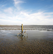 A bicycle leaning against one of the bronze statues of Antony Gormley's Another Place installation at Crosby, Merseyside at the mouth of the river Mersey. The Mersey is a river in north west England which stretches for 70 miles (112 km) from Stockport, Greater Manchester, ending at Liverpool Bay, Merseyside. For centuries, it formed part of the ancient county divide between Lancashire and Cheshire.