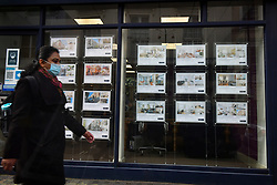 © Licensed to London News Pictures. 03/03/2021. London, UK. A member of the public wearing a face mask walks past property advertisements in the window of an estate agents in Bayswater, west London. Chancellor Rishi Sunak will later deliver a  budget aimed at repairing damage to the UK economy caused by COVID-19. Photo credit: Ben Cawthra/LNP