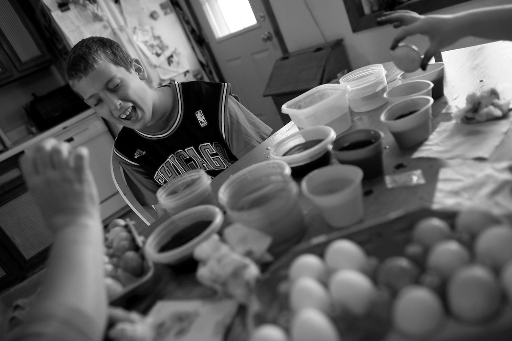 Parker Roos, who suffers from Fragile X, shares a laugh with his mother Holly and his sister Allison as they dye Easter eggs at their home in Canton, Illinois, April 4, 2012.  REUTERS/Jim Young