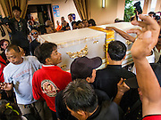 28 APRIL 2014 - BANGKOK, THAILAND: The coffin bearing Kamol Duangphasuk, 45, is brought into the crematorium at Wat Samian Nari during his funeral in Bangkok. Kamol was a popular poet who wrote under the pen name Mai Nueng Kor Kunthee. Kamol had been writing since the 1980s and was an outspoken critic of the 2006 coup that deposed Thaksin Shinawatra. After the 2010 military crackdown against the Red Shirts he went into temporary self imposed exile fearing for his safety. After he returned to Thailand he organized weekly protests against Thailand's Lese Majeste laws, which he said were being used to stifle dissent. Kamol was shot and murdered on April 23. The assailants are still at large but the murder is thought to be political.     PHOTO BY JACK KURTZ