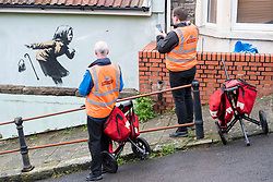© Licensed to London News Pictures; 10/12/2020; Bristol, UK. Postmen view and take photos of a mural in the style of Banksy showing a woman coughing out her dentures on a wall in Vale Street during the Covid-19 coronavirus pandemic in England. With England under a three-tier system Bristol is in Tier 3. With a roughly 22-degree gradient incline, Vale Street in the Totterdown area of Bristol is said to be England's steepest street. Photo credit: Simon Chapman/LNP.