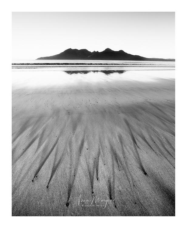 Radiating black sand streaks on beach on Eigg looking towards Isle of Rum, Scotland