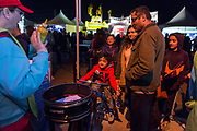AARP's Kristin Walus adds paint to the spin art bikes as Varun Tata rides at the AARP Block Party at the Albuquerque International Balloon Fiesta in Albuquerque New Mexico USA on Oct. 7th, 2018.