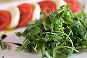 Arugula and Caprese salad, a popular Italian dish, served in a bistro in Montepulciano (Tuscany), Italy.