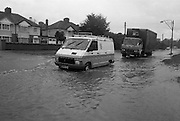 """Flooding at the Dodder..1986..26.08.1986..08.26.1986..28th August 1986..As a result of Hurricane Charly (Charlie) heavy overnight rainfall was the cause of severe flooding in the Donnybrook/Ballsbridge areas of Dublin. In a period of just 12 hours it was stated that 8 inches of rain had fallen. The Dodder,long regarded as a """"Flashy"""" river, burst its banks and caused great hardship to families in the 300 or so homes which were flooded. Council workers and the Fire Brigades did their best to try and alleviate some of the problems by removing debris and pumping out some of the homes affected..Note: """"Flashy"""" is a term given to a river which is prone to flooding as a result of heavy or sustained rainfall...Vans and trucks had an advantage going through the floodwaters,on the Lr. Dodder Road, Rathfarnham, as the sit higher off the ground"""