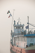 Bangladesh, Jamuna River, (called the Brahmaputra River in India) near the town of Gaibanda. The boat based Friendship non-profit organization (NGO), who provide health care and vocational traing  for locals. This is the hospital ship and the captain is raising the ship's national flag at 7 am. There is fog in the background.