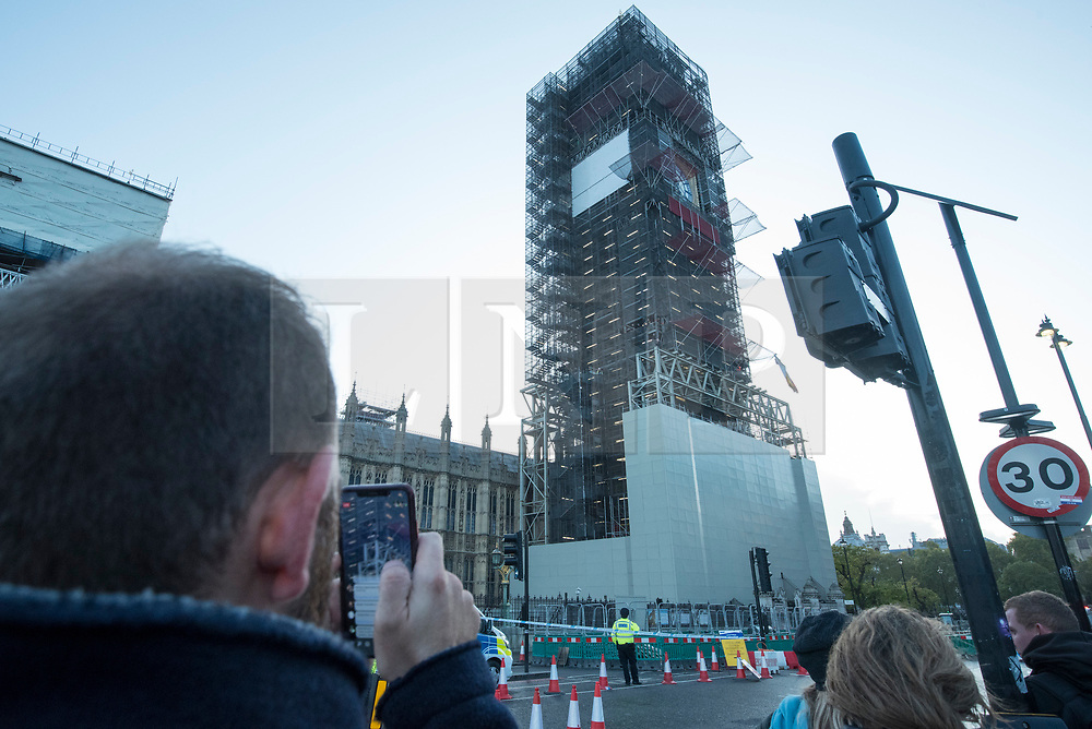 © Licensed to London News Pictures. 18/10/2019. LONDON, UK.  The public views a climate activist from Extinction Rebellion scaling the construction scaffolding of the Queen Elizabeth Tower in Westminster.  Parliament Square and the surrounding area has been brought to a standstill as police and emergency services assess the situation.  Photo credit: Stephen Chung/LNP
