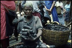 CAP HAITIEN, HAITI - A coal merchant prepares an order for waiting customers at a local market. (PHOTO © JOCK FISTICK)....