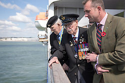 @Licensed to London News Pictures 21/05/15. Dover, Kent.94 year old Warrant Officer Arthur Taylor RAF (centre) commemorates the 75th anniversary of Operation Dynamo today aboard DFDS Ferries crossing to Dunkirk in France. by throwing a wreath into the English Channel. He is accompanied by his grandson Major Stuart Taylor RM. Operation Dynamo was the name given to the planned evacuation of Allied troops from the beaches of Dunkirk in 1940 during WWII.Photo credit: Manu Palomeque/LNP