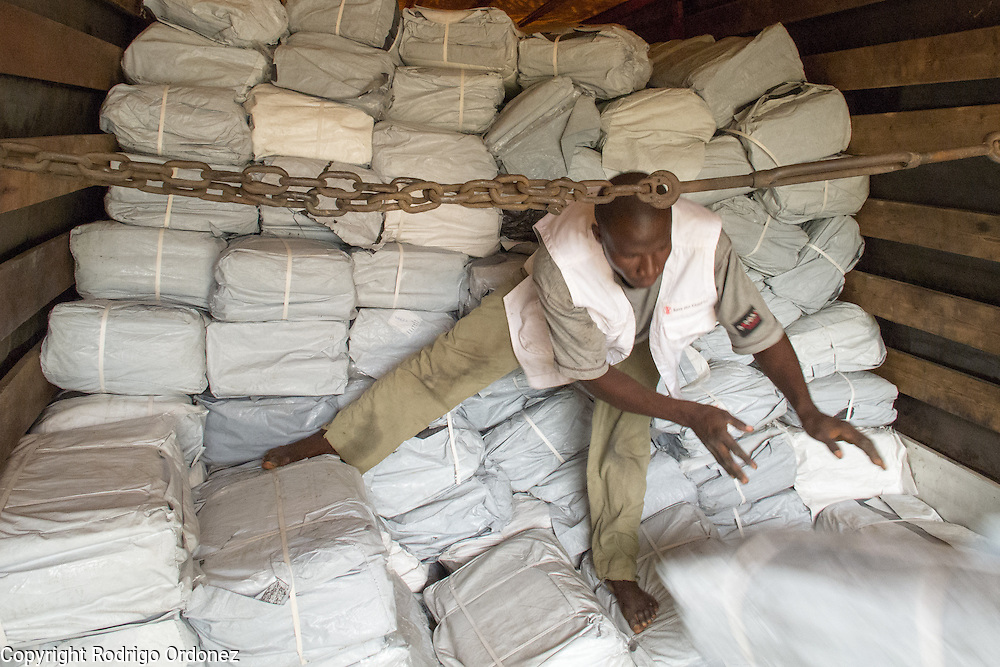 A temporary worker hired by Save the Children unloads a truck with relief items in Man, western Côte d'Ivoire. <br /> Save the Children chartered a cargo plane carrying urgently needed items, including plastic sheeting, mosquito nets, buckets and water purification tablets. The children's charity will be handing out these basic supplies to 5,000 families displaced by conflict in western Côte d'Ivoire to help prevent the spread of diseases.