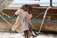 Two little girls on a makeshift swing on the beach in Nungwi, Zanzibar, Tanzania