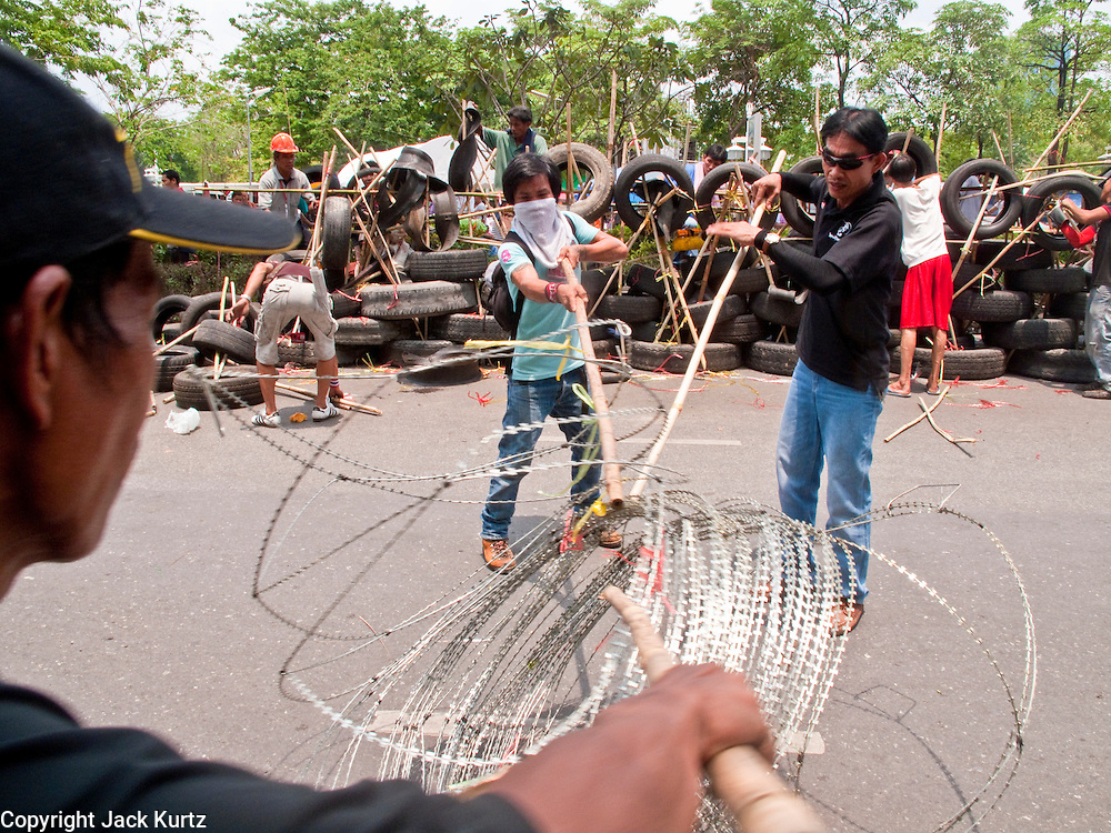 """May 2 - BANGKOK, THAILAND: Red Shirt protestors roll up """"razor wire"""" to move it to their new barricades. The Red Shirts moved  their barricades in the Sala Daeng Intersection in Bangkok Sunday further away from King Chulalongkorn Memorial Hospital after a threat that the government would move them out if they didn't move themselves. The move gave people full access to the hospital. The stand off between the Red Shirts and the government enters its third month in May. The Red Shirts continue to call for Thai Prime Minister Abhisit Vejjajiva to step down and dissolve parliament and demand the return of ousted Prime Minister Thaksin Shinawatra.   PHOTO BY JACK KURTZ"""