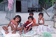 The poor health of these smiling children is evident from the runny noses and sores on legs. They live in a shack with no electricity or running water & play on a beach strewn with human feces. Malapascua, central Philippines, Vizcayan Sea, Western Pacific Ocean