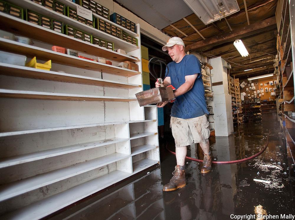 Chad Hanzelka of Cedar Rapids helps clean out Hartwick Marina in Delhi, Iowa on Monday, July 26, 2010.