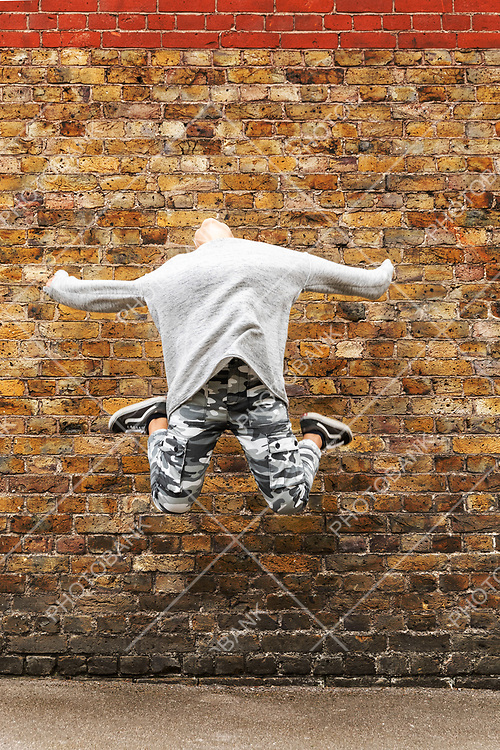 Young girl jumps in front of a brown brick wall. Front view. Nobody inside