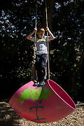 Boy swings on rope in risk averse playground called The Land on Plas Madoc Estate, Ruabon, Wrexham, Wales.